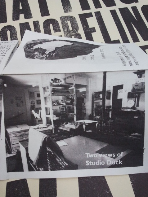 A view of Studio Duck as documented in Snail no. 2, November 2011.  Behind the zine: an Ampersand Duck poster.