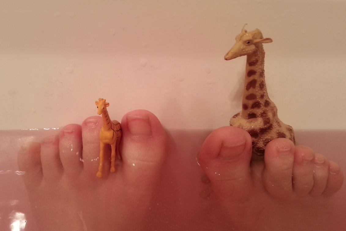 Giraffe toys and toes in the tub